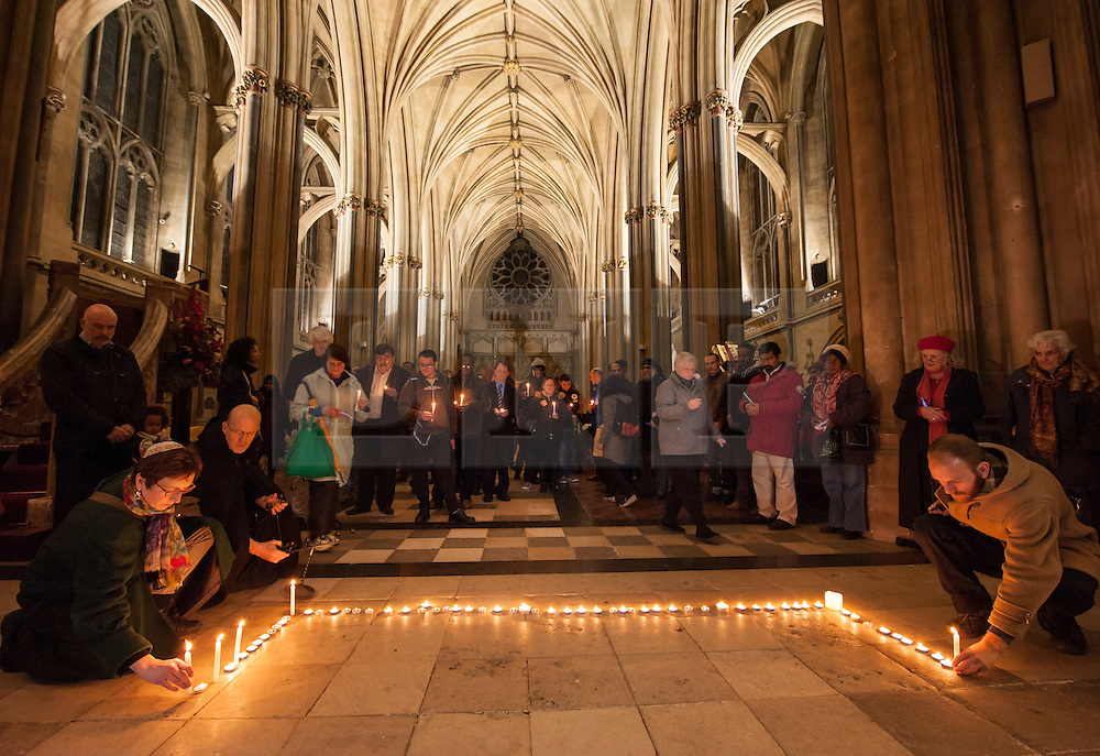 """© Licensed to London News Pictures. 17/11/2015. Bristol, UK.  Vigil for the victims of the Paris terrorist attacks at Bristol Cathedral with religious and community leaders.  The Muslim community in Bristol organised a candle-lit vigil for all faiths and backgrounds at Bristol Cathedral to show solidarity with the victims of the Paris attacks which are claimed by IS (Islamic State).  The management and Imaam's of Bristol's Easton Jamia Masjid, Bristol's biggest mosque, released a statement saying they have been shocked and saddened by the attacks on innocent people in France. """"We strongly condemn the terrorist atrocities in France, these sickening crimes are an attack against all of humanity.  As a local Muslim place of worship we send our condolences from our local community and congregation to the people of France.  During this very dark hour they will see compassion and solidarity from around the world"""".  Photo credit : Simon Chapman/LNP"""