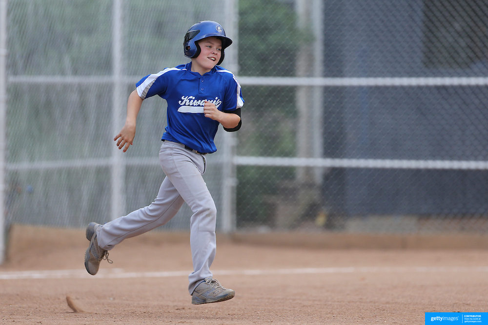 A young batter runs the bases after hitting a home run during the Norwalk Little League baseball competition at Broad River Fields,  Norwalk, Connecticut. USA. Photo Tim Clayton