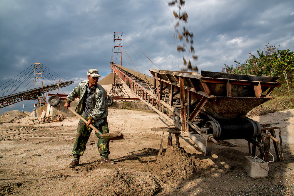 A man shovels spilled sand onto a conveyor belts which moves sand from the dredging boats to the shore for drying. The dredged sand is sold locally and to large scale construction sites in nearby major cities such as Kunming and Jinhong.