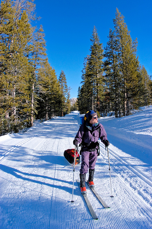 Backcountry skier pulling a sled on the Glacier Point Road (Sentinel Dome in background), Yosemite National Park, California