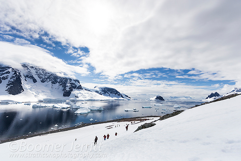 Visitors to Danco Island hike up a snowfield against a backdrop of icebergs and glaciers.  Danco Island, Antarctic Peninsula, Antarctica.