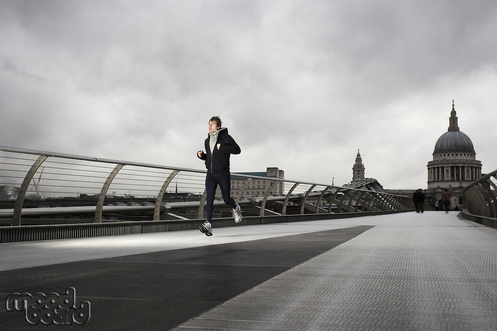 Young male runner on the Millenium Bridge with St Paul's in the background