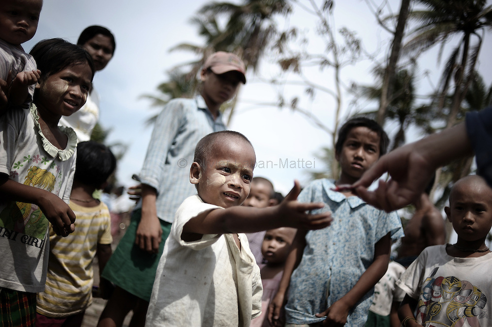 Young children from the village of Chaung Lin receive food thrown from a boat by locals on May 23, 2008 in the isolated area of Kanzeik in the Irrawaddy Delta region -- an area only accessible by boat which has received neither government nor foreign aid. Voters in regions devastated by the cyclone, many hungry and destitute, cast ballots on May 24 in a referendum that many said was meaningless because Myanmar's junta has already declared victory.