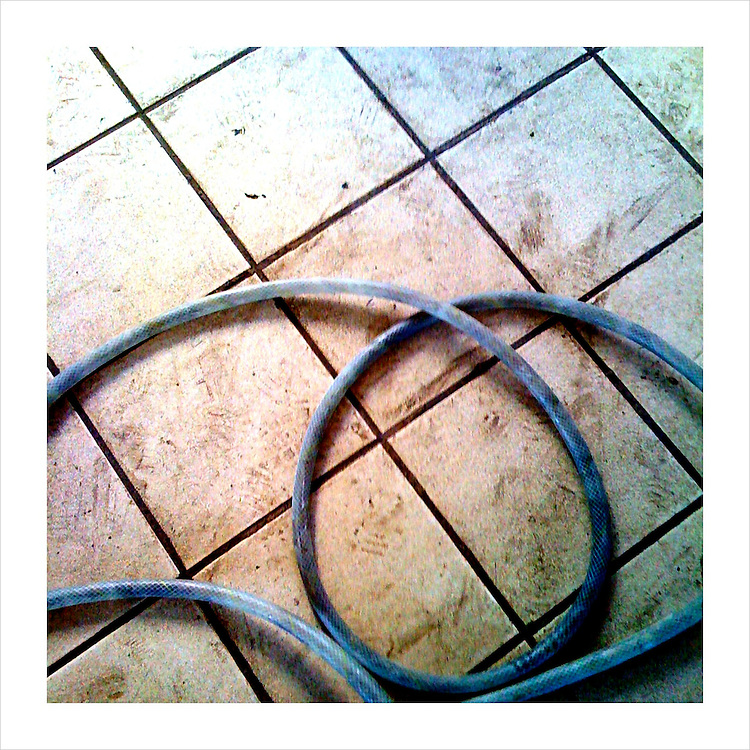 A coiled water hose on the floor inside of the Tres Mujeres tequila distillery, in Jalisco, Mexico. (iPhone image) --- Image created for http://tastetequila.com