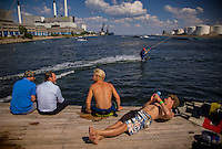 Copenhagen, Denmark- JULY 24, 2014:  Onlookers wait their turn as a wakeboarder gldes over the harbour water at Copenhagen Cable Park, where a series<br /> of suspended cables tow riders around the aquatic course. CREDIT: Chris Carmichael for The New York Times