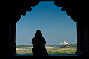 Tourist sits to view Taj Mahal from Khas Mahal Palace at Agra Fort, India