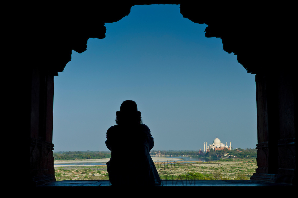 Tourist sits to view Taj Mahal from Khas Mahal Palace at Agra Fort, India