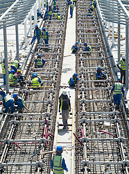 Construction workers laying railway tracks for new light rail / metro line in marina district of New Dubai United Arab Emirates