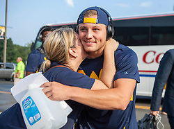 Sep 5, 2015; Morgantown, WV, USA; West Virginia Mountaineers quarterback Skyler Howard hugs a fan as he enters the stadium to play the Georgia Southern Eagles at Milan Puskar Stadium. Mandatory Credit: Ben Queen-USA TODAY Sports
