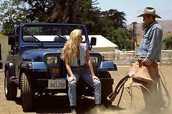 cowboy talking to a blonde woman sitting on a jeep