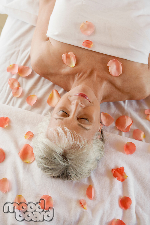 Woman Relaxing at the Spa Surrounded by Rose Petals