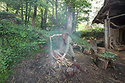Elodie Michel, ropemaker, at work with a length of rope at the fire, outside the rope makers' workshop at the Chateau de Guedelon, a castle built since 1997 using only medieval materials and processes, photographed in 2017, in Treigny, Yonne, Burgundy, France. The Guedelon project was begun in 1997 by Michel Guyot, owner of the nearby Chateau de Saint-Fargeau, with architect Jacques Moulin. It is an educational and scientific project with the aim of understanding medieval building techniques and the chateau should be completed in the 2020s. Picture by Manuel Cohen