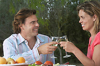 Couple toasting in garden fruit on table