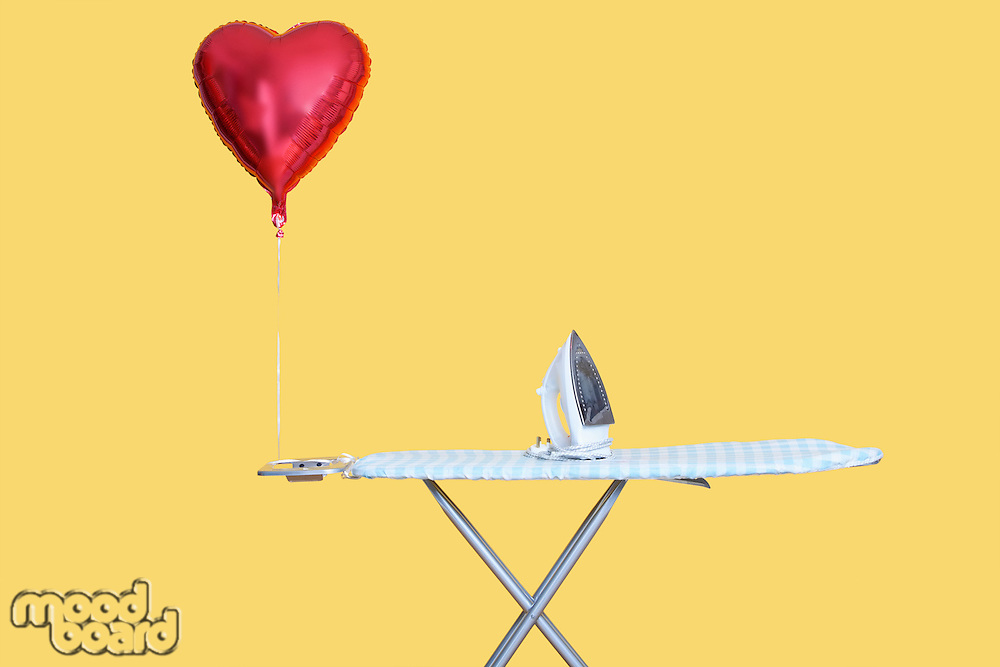 Heart shaped balloon tied to ironing board over yellow background