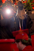 Graduate student gets her photo taken after picking her diploma.