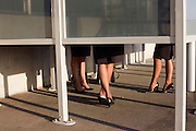"The legs of anonymous airline employees are seen from below a smoking screen that obscures their faces outside Heathrow Airport's Terminal 5 building. In afternoon sunshine, the women wear their airline uniforms and are sharing an off-duty puff on their cigarettes as part of their working shift at this international aviation hub. Without seeing their upper-bodies, we imagine their conversation and gossip. From writer Alain de Botton's book project ""A Week at the Airport: A Heathrow Diary"" (2009)."