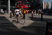 A cyclist pedals over Cannon Street in the City of London, UK.