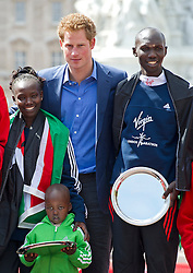 © London News Pictures. 22/04/2012. London, UK. HRH Prince Harry presenting the winners trophy to Wilson Kipsang (right) and Mary Keitany of Kenya (left with her son)  who came first in the elite races at the 2012 Virgin London Marathon on April 22, 2012. Photo credit : Ben Cawthra /LNP