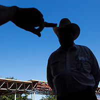 USA, New Mexico, Albuquerque, Silhouette of man in cowboy hat standing in paddock before start of thoroughbred horse races at The Downs at Albuquerque race track
