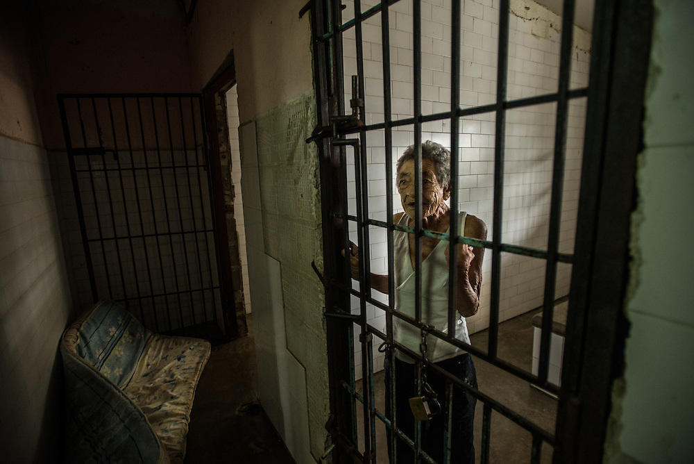 BARQUISIMETO, VENEZUELA - JULY 28, 2016: Schizophrenic patient, <br /> Maria Guzman looks out from the bars of her solitary confinement cell. She is not violent, but was locked up because nurses found her eating other patient&rsquo;s feces in the patio of the women&rsquo;s ward, so they locked her in isolation to prevent her from doing it again.  Her age is unknown, but staff estimate she is between 70 and 80 years old.  The economic crisis that has left Venezuela with little hard currency has also severely affected its public health system, crippling hospitals like El Pampero Psychiatric Hospital by leaving it without the resources it needs to take care of patients living there, the majority of whom have been abandoned by their families and rely completely on the state to meet their basic needs, and who could live much more fulfilling lives if they had the medicines that they need. The hospital does not even have basic hygiene or cleaning supplies.  There is no soap, no shampoo, no tooth paste, no toilet paper.  Patients relieve themselves in the common areas and patio area, and clean themselves only with water. Nearly every patient is infected with scabies because they do not have the resources to bathe properly or to have their threadbare, misfitted clothes washed as often as needed. To make matters worse, the hospital only has running water a few hours a day.  PHOTO: Meridith Kohut