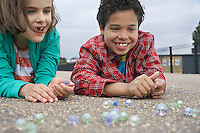 Boy and girl (7-9) playing marbles lying in playground