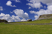 A glorious deep blue sky with dramatic cumulus clouds over a traditional stone field barn and Robin Proctor's Scar near Austwick, Yorkshire Dales.<br />
