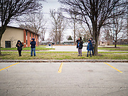 """26 MARCH 2020 - DES MOINES, IOWA: People practice """"social distancing"""" while they wait for lunch distribution at Weeks Middle School. Des Moines Public Schools (DMPS) started distributing hot lunches Thursday, the first day students were supposed to return to school. Schools will now remain closed until 13 April. On Thursday morning, 24 March, Iowa reported 175 confirmed cases of the Coronavirus (SARS-CoV-2) and COVID-19. Restaurants, bars, movie theaters, places that draw crowds are closed until 07 April. The Governor has not ordered """"shelter in place""""  but several Mayors, including the Mayor of Des Moines, have asked residents to stay in their homes for all but the essential needs. People are being encouraged to practice """"social distancing"""" and many businesses are requiring or encouraging employees to telecommute.         PHOTO BY JACK KURTZ"""