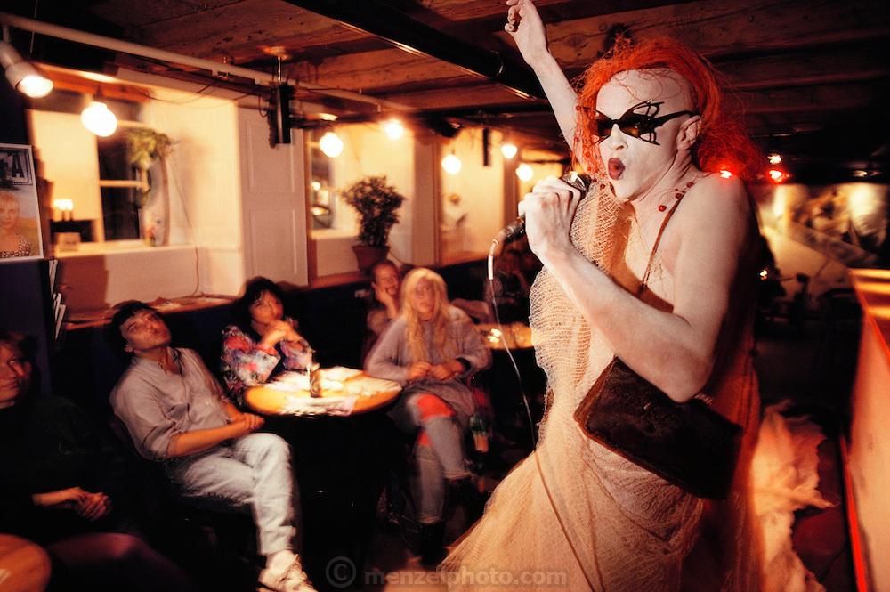"A performance artist calling his act ""Living Sculpture"" performs at the bar of the Café Rosa. Copenhagen, Denmark."