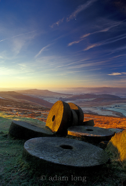 A frosty midwinter dawn breaks over the abandoned millstones below Stanage in The Peak District