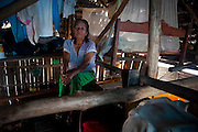 A long time resident of Belen sits amongst the rafters of her home and beside her bed which now hangs above the rising water. Image © Jonah Markowitz/Falcon Photo Agency