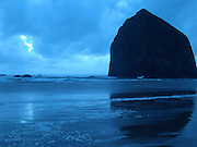 Haystack Rock reflection in the high tide during sunset at Cannon Beach, Oregon, USA.  Haystack Rock, a protected wildlife refuge, is a Pacific coast landmark towering 235 ft. above the beach.