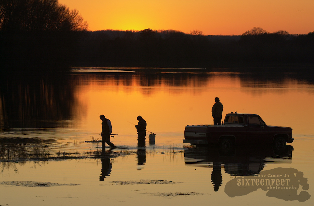 Photo by Gary Cosby Jr.  Three men fish in flooded Crabtree Slough in the Wheeler National Wildlife Refuge in Decatur, Alabama as the sun sinks below the horizon.
