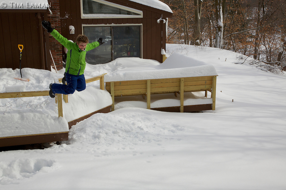 A boy playing in the snow after a blizzard.