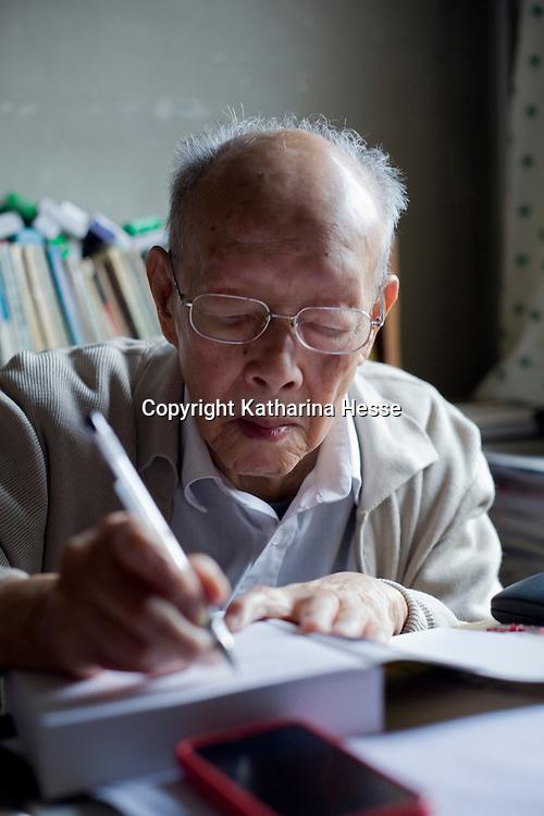 """BEIJING, 10.15.2012 :  Zhou Youguang signiert ein Buch, waehrend sein Sohn zuschaut. Zhou, Jahrgang 1906, ist der Erfinder des  """"Pinyin"""" , einer Umschrift  fuer Chinesische Zeichen."""
