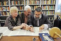 Joyce and Harold Gordon, left, symbolically help Rabbi Moshe Druin, a sofer (scribe), write in Temple Beth-El's Torah scrolls on Sunday.