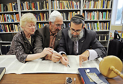 Joyce and Harold Gordon, left, symbolically help Rabbi Moshe Druin, a sofer (scribe), write in Temple Beth-El's Torah scrolls on Sunday.