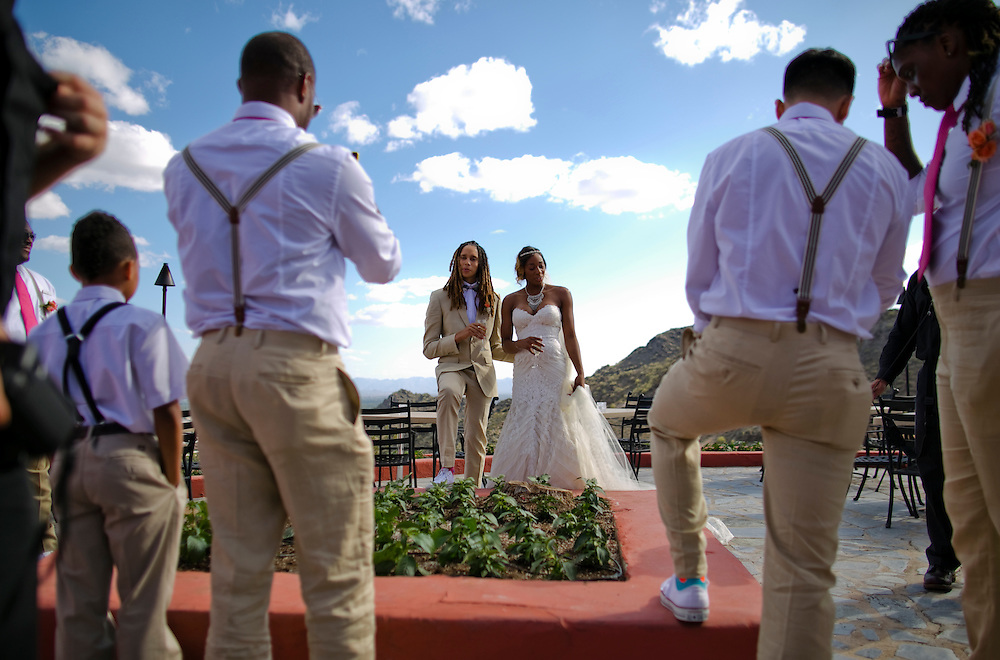 WNBA stars Glory Johnson, right and Brittney Griner pose for photographs during their wedding ceremony at the Pointe Hilton Tapatio Cliffs Resort in Phoenix, Ariz. on May 8, 2015.