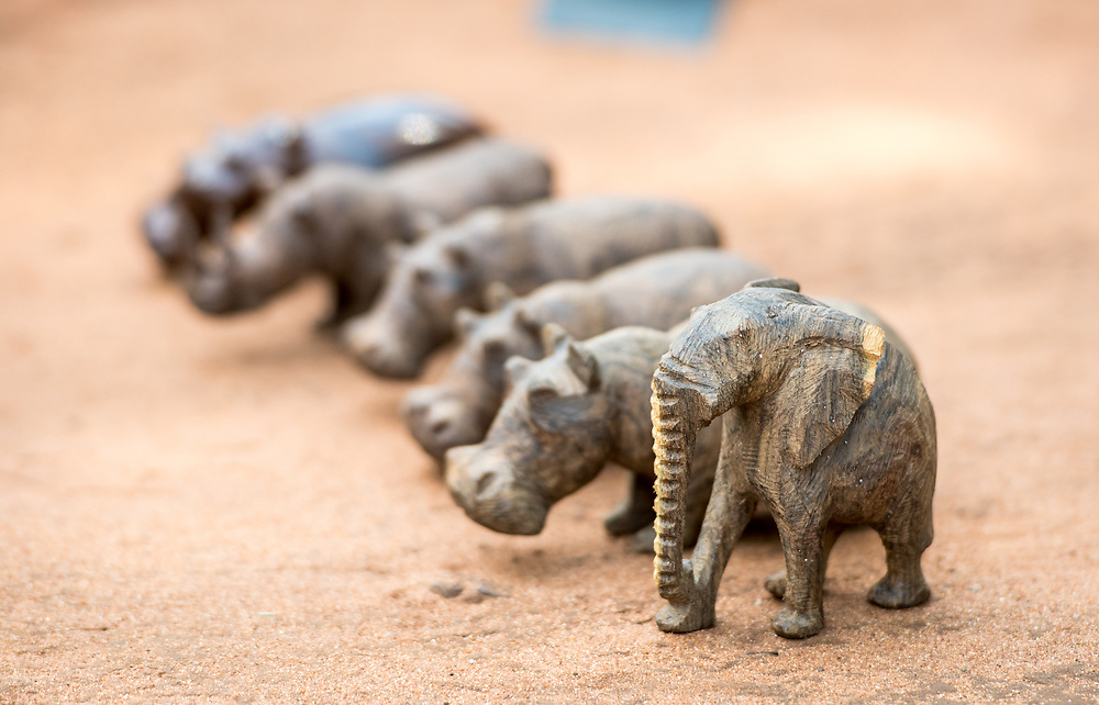 Handcrafted wooden figurines of various animals lined up in a row, Mukuni Village, Zambia