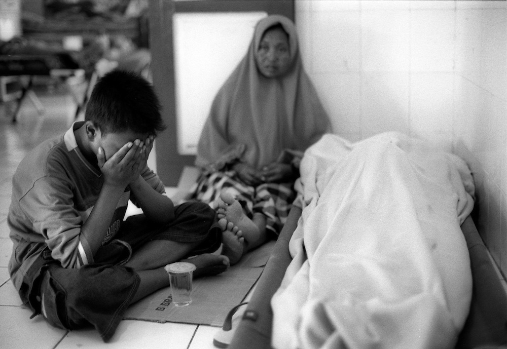 A woman and her son mourn beside the body of her husband, a victim of the Tsunami that claimed the lives of many thousands of people. Kesdam Hospital, Banda Aceh January 2005