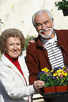 Elderly man and senior woman holding tray with potted flowers