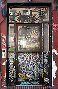 The entrance to an apartment building in the East Village of Manhattan.  It is covered in graffiti.