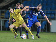 Kingsley James (Halifax) challenges for the ball with Will Hatfield (Guiseley) while the Ollie Yates (referee) watches on during the Conference Premier League match between FC Halifax Town and Guiseley at the Shay, Halifax, United Kingdom on 5 December 2015. Photo by Mark P Doherty.