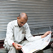 Indian man reading newspaper in Chandni Chowk, Old Delhi