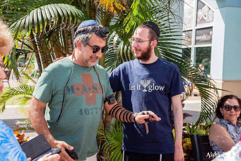 Yitzchok Stell, right, helps Ian Simmons of Boynton Beach put on Tefillin, small boxes containing verses of the Torah.  Members of the Chabad Lubavitch of the Virgin Islands hand out menorahs in Crown Bay to visiting tourists wishing to celebrate Chanukah.   8 December 2015.  © Aisha-Zakiya Boyd