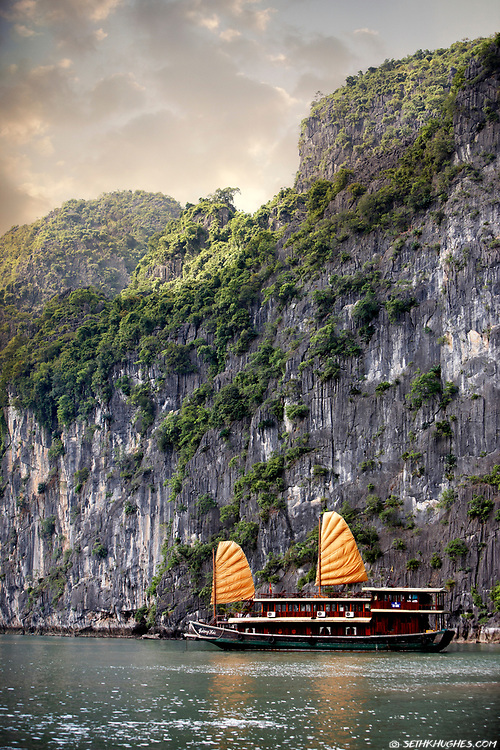 A Vietnamese junk boat cruises Ha Long Bay next scenic limestone cliffs.