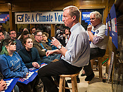 13 JANUARY 2020 - WEST DES MOINES, IOWA: TOM STEYER, left, speaks to a crowd of about 70 people at a house party in West Des Moines Monday night. CHANNING DUTTON, a Des Moines attorney, right, hosted Steyer. The main issue was climate change, which Steyer has said is his top priority. Steyer, a California businessman, is campaigning to be the Democratic nominee for the US Presidency in 2020. Iowa holds the first selection event of the 2020 election cycle. The Iowa Caucuses are Feb. 3, 2020.               PHOTO BY JACK KURTZ