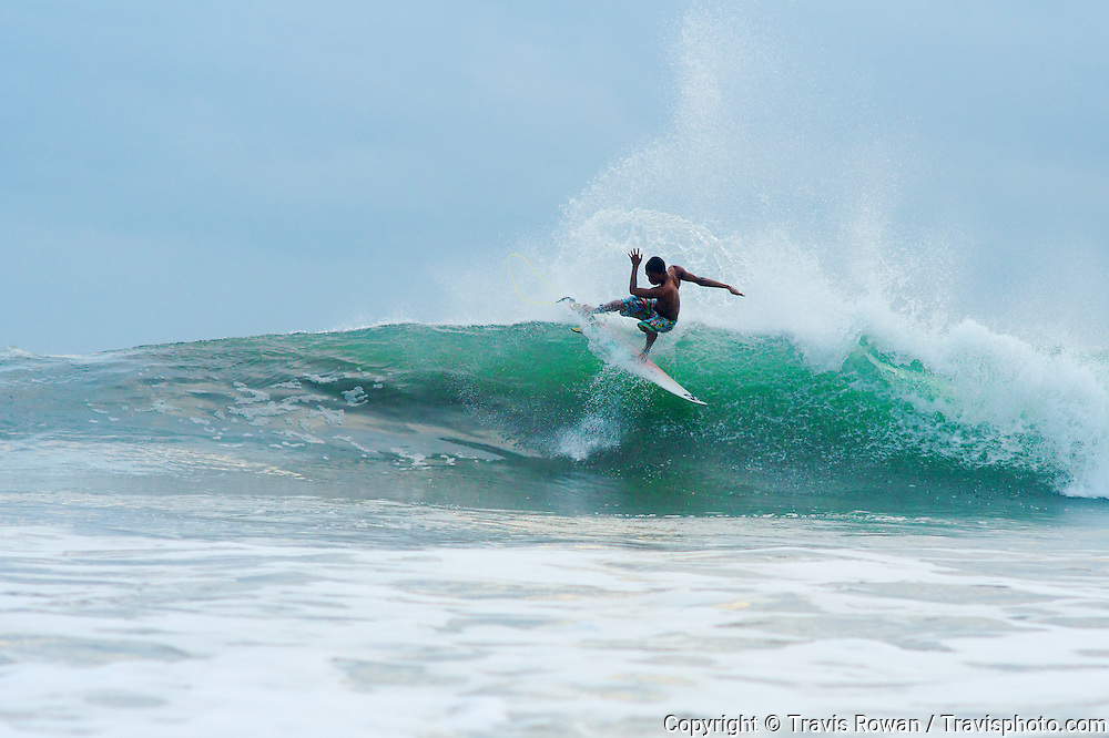 Professional Balinese surfer, Dedi Santoso in action on Kuta beach, Bali.