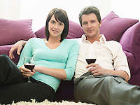 Young couple sitting by sofa with wine