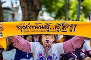 16 MAY 2014 - BANGKOK, THAILAND: A PDRC supporter holds up a banner supporting Suthep Thaugsuban and the Thai monarchy during a picket of the Thai Parliament complex. Thousands of protestors from the People's Democratic Reform Committee (PDRC) surrounded the Thai Parliament complex Saturday to pressure the Thai Senate to select an interim Prime Minister to replace ousted former PM Yingluck Shinawatra. The Senate decided not to appoint an interim PM of their own and announced a meeting with the current interim Prime Minister. The protestors left the parliament complex and threatened to return in larger numbers if the Senate doesn't act. The Senate appointment of an acting PM could plunge Thailand into chaos since there is already an interim Prime Minister from the ruling Pheu Thai party.     PHOTO BY JACK KURTZ