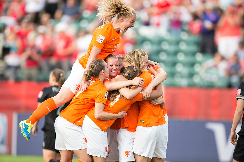 The Netherlands' Petra Hogewoning  jumps on her teammates, celebrating the goal by Lieke Martens during the first half of their Group A football match against New Zealand at Commonwealth Stadium on the opening day of the FIFA Women World Cup in Edmonton, Canada on June 6, 2015.   AFP PHOTO/GEOFF ROBINS